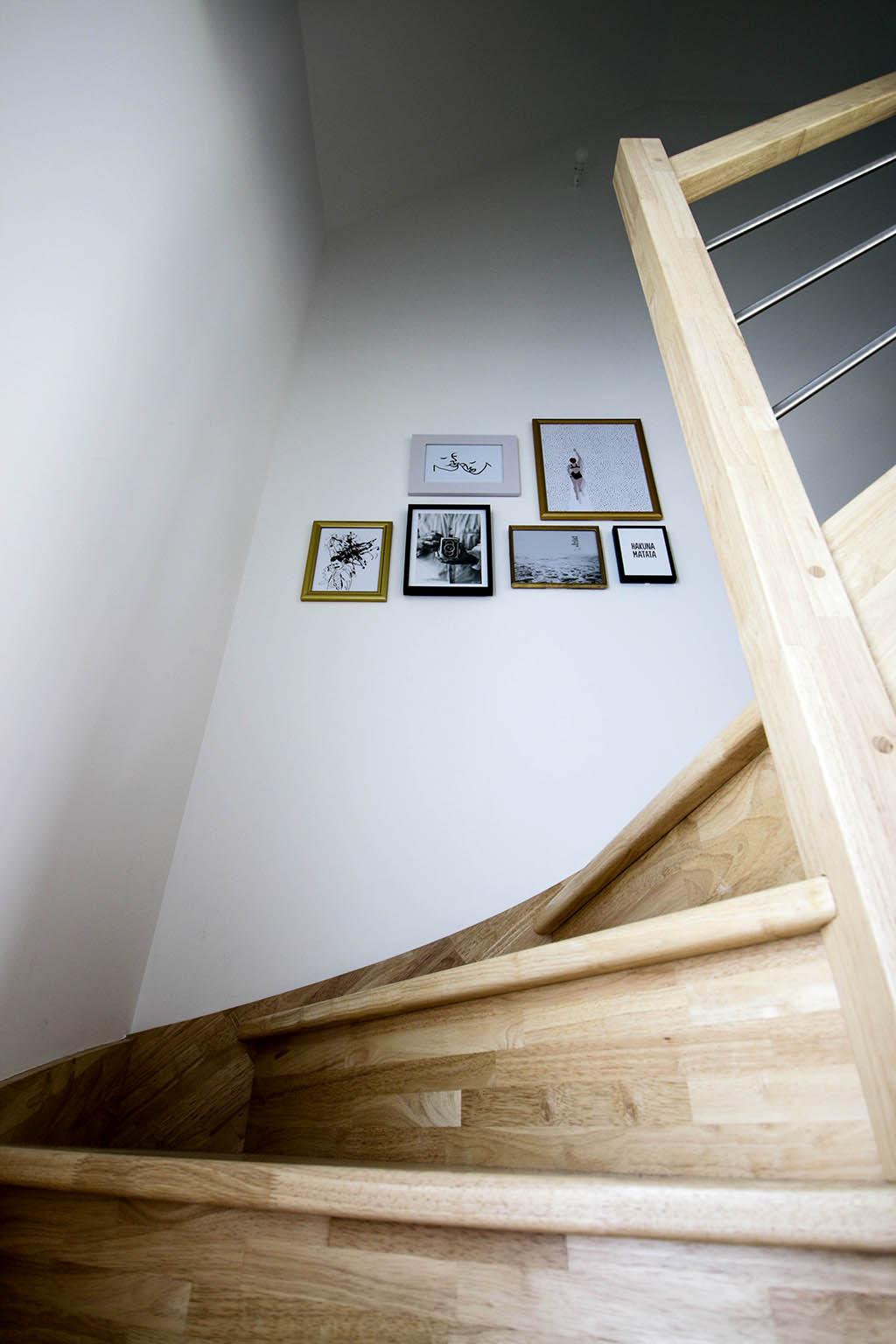 mur de cadres dans un escalier design en bois