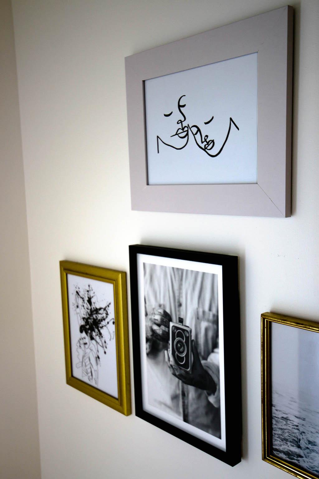 mur de cadres avec photos en noir et blanc