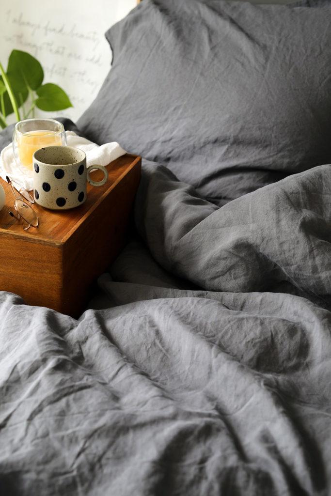 lit avec housse de couette en lin et tasse de café